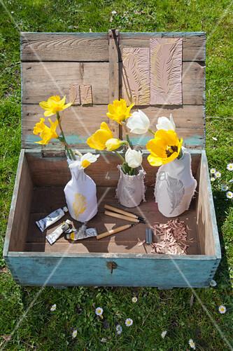 Alte Holzkiste mit Tulpen und Narzissen in Vasen mit Stoffbezug