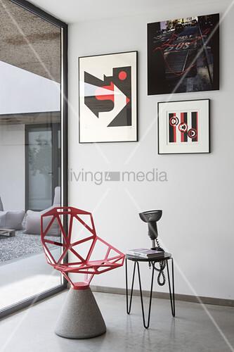Roter, Designerstuhl mit Zementfuß und Beistelltisch unter moderne Kunst