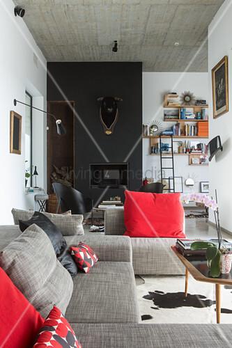 Graue Polstergarnitur mit roten Kissen, im Hintergrund schwarze Wand mit Stierkopf und Kamin