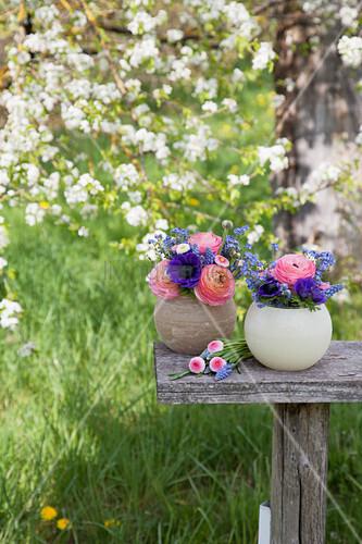 Kugelvasen mit Frühlngsblumen im Garten
