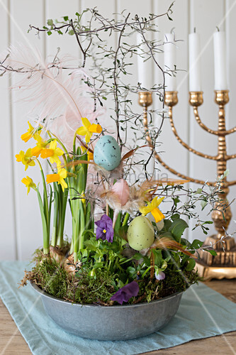 Easter eggs in bowl planted with narcissus in front of candelabra