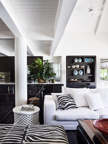 Offener Wohnraum mit weißem Polstersofa, Kissen und Polsterhocker in Zebra-Look
