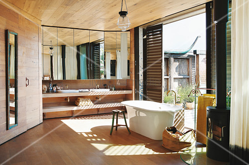Free-standing bathtub in spacious bathroom with access to terrace