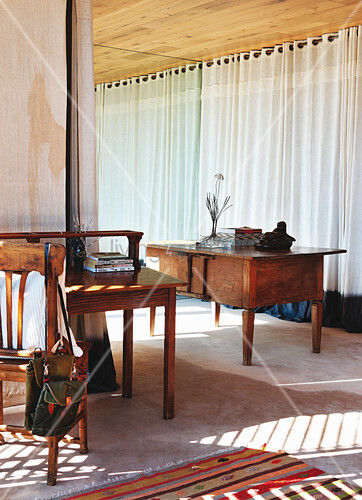 Antique table in front of windows with floor-length curtains