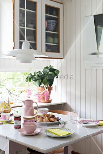 Breakfast table set in pastel shades in kitchen