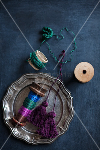 Reels of thread, hand-made tassels and thread wrapped around cardboard tube