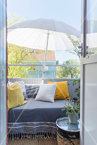 Tagesbett mit Kissen und Sonnenschirm auf dem Balkon