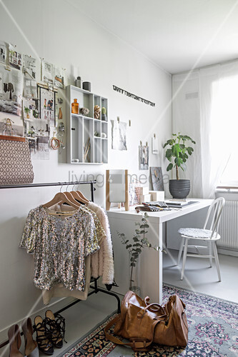 Women's clothing on rack below pinboard and display case on wall and next to desk and chair