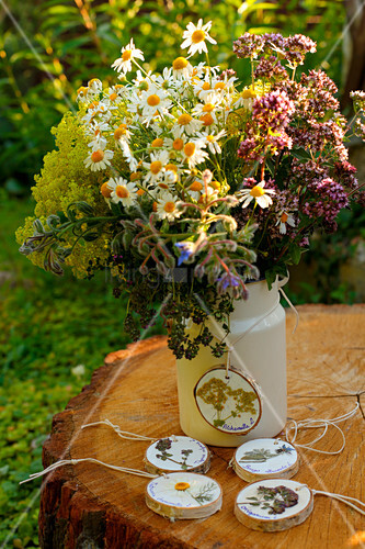 Flowering herbs in milk jug with tag made from wooden disc