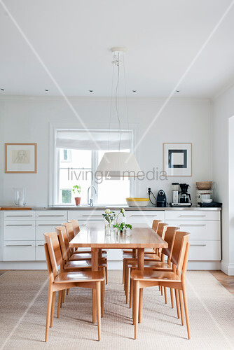 Pale wooden chairs and dining table in front of white kitchen counter