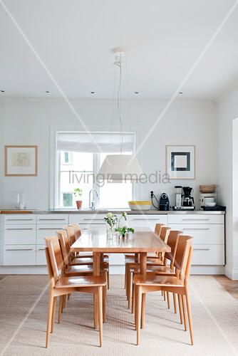 Stühle und Esstisch aus hellem Holz vor weißer Küchenzeile