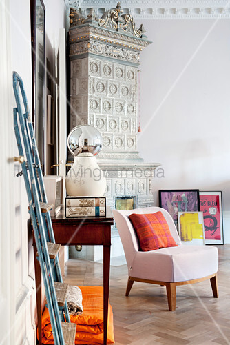 Pale pink easy chair in front of antique tiled stove in corner
