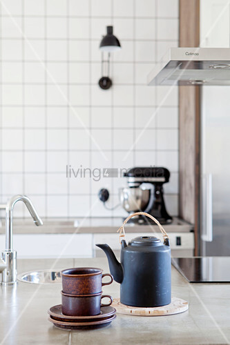 Black teapot and stacked teacups on island counter