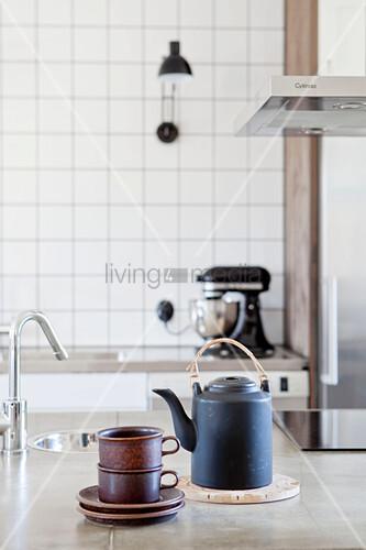 Schwarze Teekanne und gestapelte Tassen auf der Kochinsel