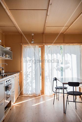 Küche mit Holzverkleidung und weißen Vorhängen an der Terrassentür