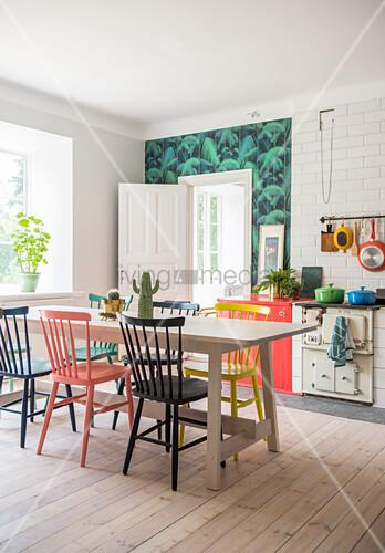 Bunte Windsorstühle um den Esstisch in der Küche mit Holzboden