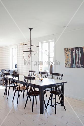 Schwarzer Esstisch mit Windsorstühlen auf hellem Holzboden