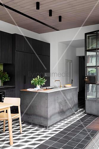 Beton-Kücheninsel vor schwarzer Einblauküche