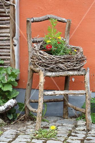Aus Reben geflochtener Kranz auf rustikalem Stuhl aus Ästen