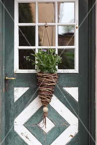 Blumenampel aus Korbgeflecht an ländlicher Haustür