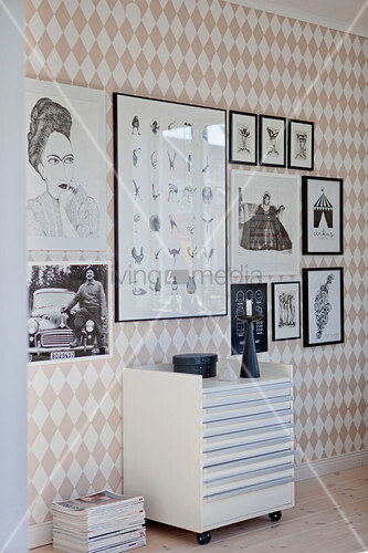 Plan chest on wheels below gallery of pictures on wall with diamond-patterned wallpaper