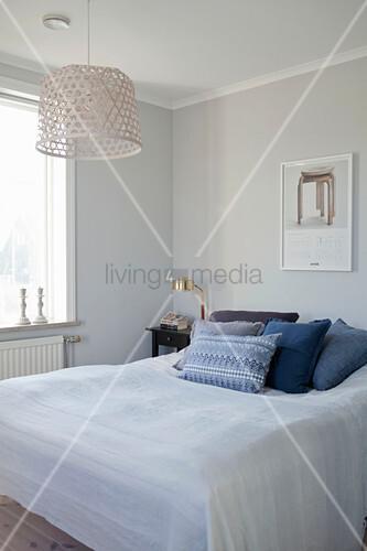 Blaue Kissen auf dem Bett im schlichten Schlafzimmer