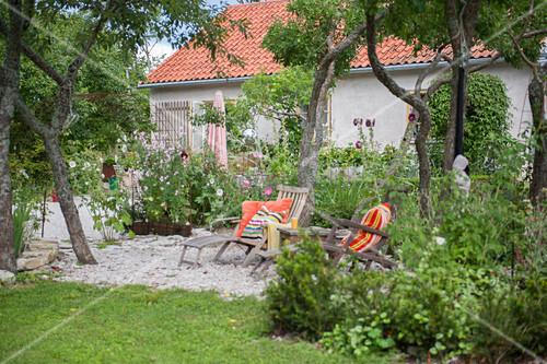 Loungers on terrace in summery garden