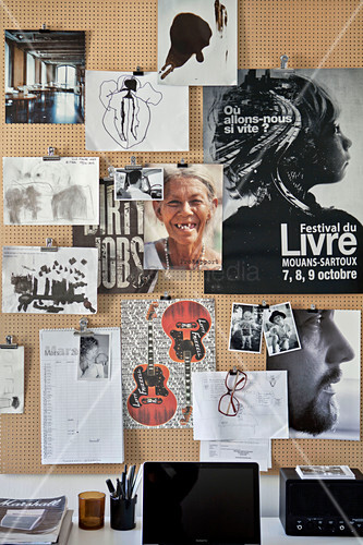 Posters, photos and drawings on pinboard made from perforated panel