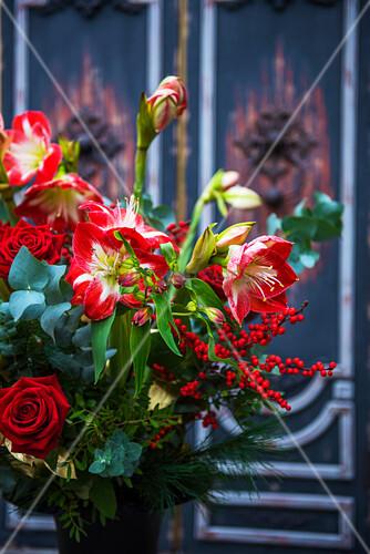 Winterlicher Strauß mit roten Blumen wie Rose und Amaryllis