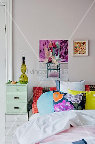 Gemusterte Kissen auf dem Bett, Schubladenschränke als Nachttisch