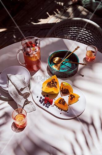 Papaya, Beeren und Erfrischungsgetränk auf dem Tisch im Freien