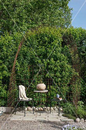 Sitzplatz unterm Bogen aus rostigen Stahlgittern im Garten