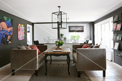 Elegant sofas and coffee table in living room with dark walls and modern artworks