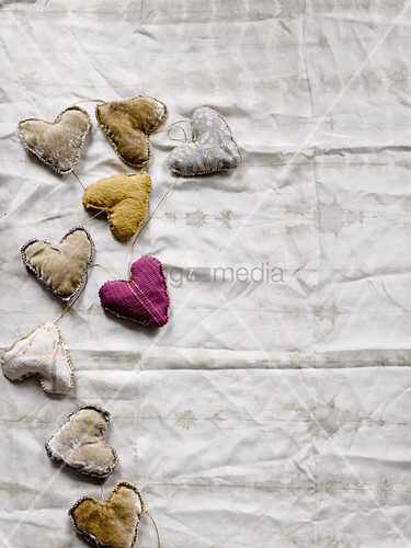 Garland of hand-sewn fabric hearts on white fabric