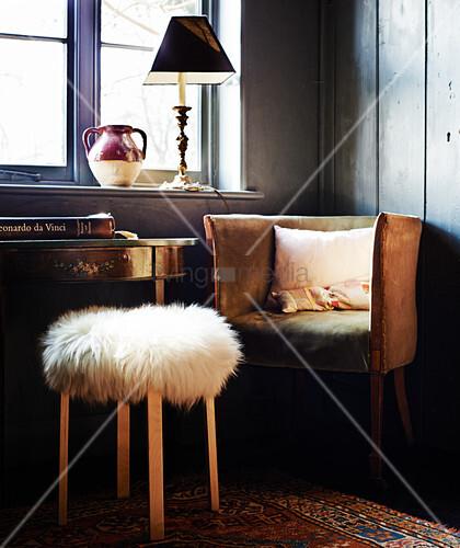 Hocker mit Fellbezug vor einem alten Sessel am Fenster