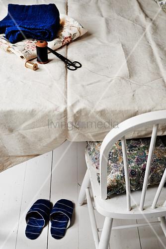Selbstgenähte Hausschuhe unter dem Tisch mit Nähzeug