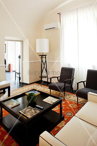 Black rectangular coffee table, black armchairs, pale sofa and standard lamp in elegant lounge