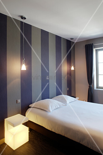 Double bed against wallpaper with broad dark stripes, pendant lamp and illuminated bedside cabinet in bedroom