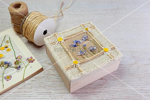 Schachtel mit gepressten Blüten und Band verzieren