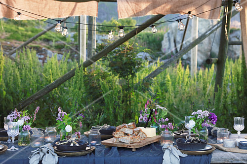 Table set for summer party below wooden frame