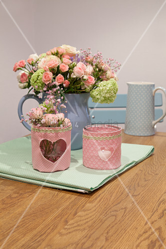 Spring flowers in old jug and candle lanterns with fabric covers