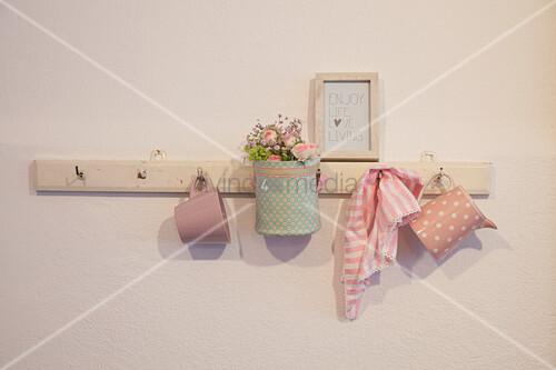 Stoffkörbchen mit Blumen und Geschirr an einer Hakenleiste