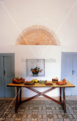 Plates of fruit on rustic wooden table on Mediterranean patterned tiled floor