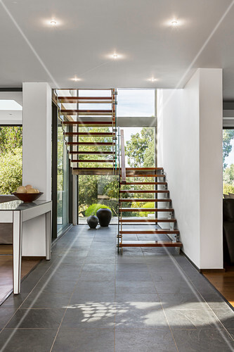 Modern free-standing staircase in front of glass wall overlooking garden