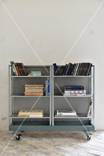 Books on simple metal shelves on castors against white wall