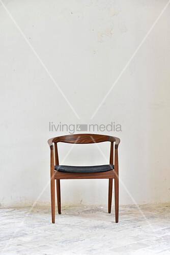 Scandinavian wooden chair against white wall