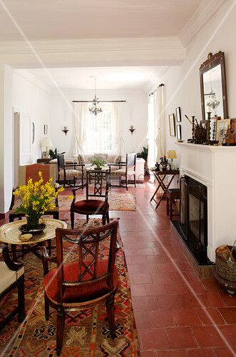 Fireplace and terracotta floor tiles in Mediterranean lounge