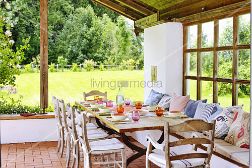Gedeckter Tisch auf überdachter Terrasse im sommerlichen Garten