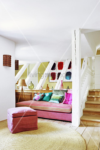 Pink sofa with colourful scatter cushions next to foot of stairs