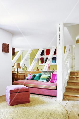 Rosafarbenes Sofa mit bunten Kissen neben der Treppe